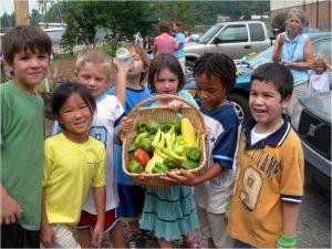 Children display their vegetable harvest from the school garden.