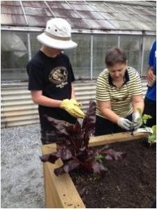 Extension Master Gardener instructs student in vegetable gardening.